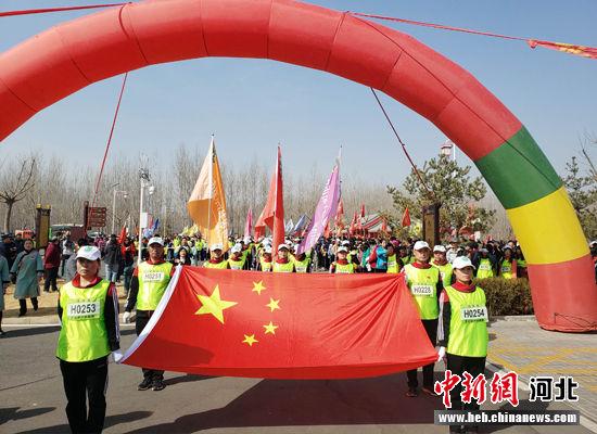 徒步爱好者们在国旗的引领下从清西陵综合服务区出发。 徐巧明 摄