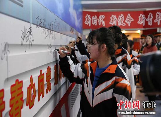学生代表在成人节宣誓仪式上签字。 李丹 摄
