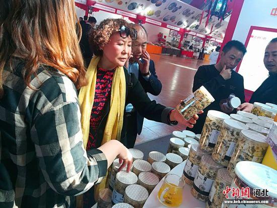 游客在巨鹿特色产品展位前选购商品。 乔娜 摄