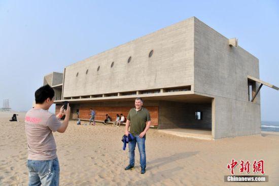 """5月15日下午,位于河北秦皇岛北戴河新区一处海边的沙滩上,一座被网友们称作""""最孤独的图书馆""""吸引着来自四面八方的读者。图为一位德国游客在图书馆外拍照留念。中新社记者 翟羽佳 摄"""