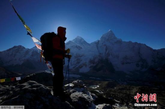 资料图为一名登山者站在珠峰前。