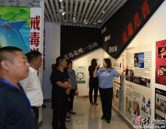 6月25日,在河北省强制隔离戒毒所戒毒教育展览室,工作人员向参观者讲解毒品的危害。