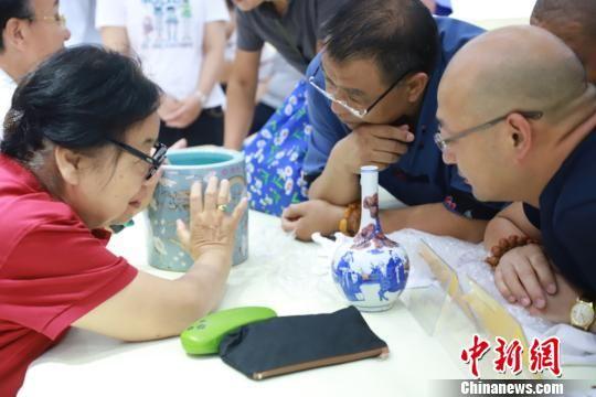 北京市文物鉴定委员会秘书长张如兰为市民鉴定收藏品。供图