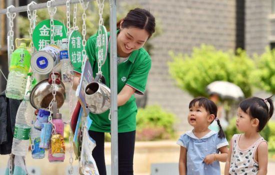7月4日,在石家庄市桥西区红旗街道紫东苑小区,志愿者将垃圾分类的样品进行整理,准备为小区居民讲解。