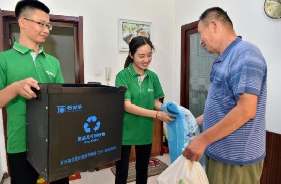7月4日,在石家庄市桥西区红旗街道紫东苑小区,志愿者给社区居民送上统一制作的垃圾回收箱,帮助居民进行垃圾分类。