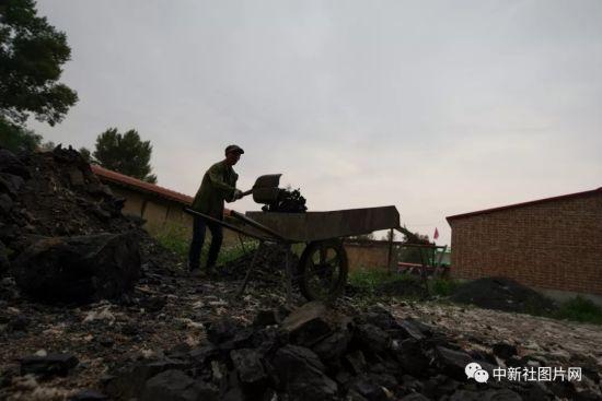 6月27日,工匠正在装运烧制青砂器用的木炭。中新社记者 贾天勇 摄