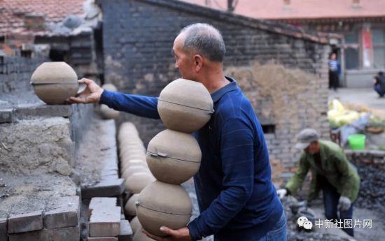 6月27日,河北省张家口蔚县青砂器烧制作坊,青砂器第四代传人王启杰正在摆放青砂器模具。中新社记者 韩冰 摄
