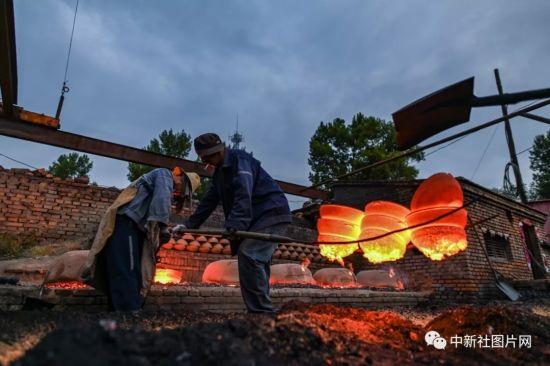 6月27日,在河北省张家口市蔚县白河东村,蔚州青砂器第五代传承人王龙磊在与工匠们烧制青砂器。中新社记者 何蓬磊 摄