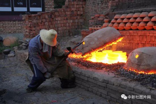 6月27日,河北省张家口蔚县青砂器烧制作坊,第五代传承人王龙磊正在掀开锅盖。中新社记者 宁南 摄