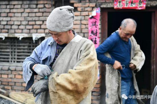 6月27日,蔚州青砂器第五代传承人――王龙磊(左)与父亲――蔚州青砂器第四代传承人王启杰换上工作服准备取出烧制好的青砂器。中新社记者 张兴龙 摄
