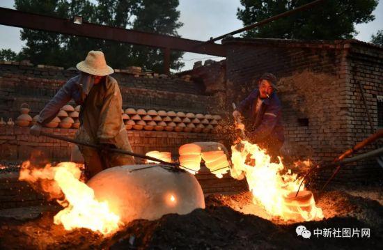 6月27日,在河北省张家口市蔚县白河东村蔚州青砂器作坊内,工匠们正在取出烧制好的青砂器。中新社记者 张兴龙 摄