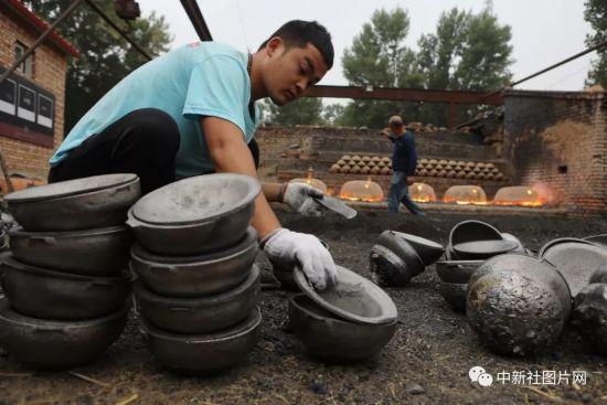 6月27日,工匠正在对烧制而成的砂锅进行验质打包。中新社记者 李国庆 摄
