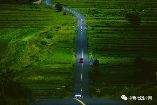 6月28日,游客驾驶车辆行驶在草原天路上。中新社记者 佟郁 摄