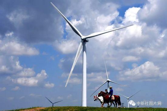 6月28日,游客骑马从风车下经过。中新社记者 姬东 摄