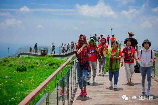 6月28日,夏季的草原天路气候宜人,吸引大量游客前来。中新社记者 佟郁 摄