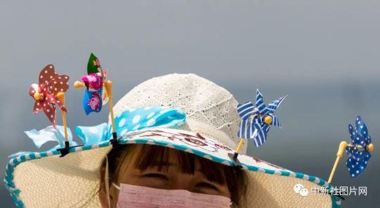 6月28日,草原天路景区,一位商贩在帽檐上夹着小风车,以别致的方式来招揽顾客。中新社记者 张畅 摄