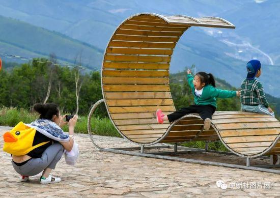 6月28日,紧邻太子城冰雪小镇项目的太舞冰雪小镇内,慕名而来的游客在山间为孩子留影。中新社记者 刘新 摄