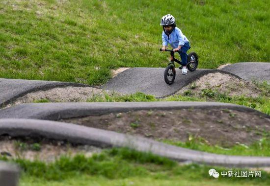 6月28日,崇礼太舞冰雪小镇内,小朋友在体验区骑行平衡车。中新社记者 刘新 摄