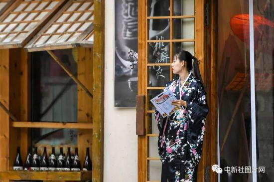6月28日,崇礼太舞冰雪小镇内,一位女服务员穿着日本和服,在酒吧门前等待游客登门。中新社记者 刘新 摄