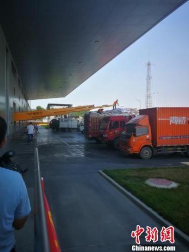 南和县一家宠物食品企业仓库外,挂着各地牌照大卡车正排队装货。 李晓伟 摄