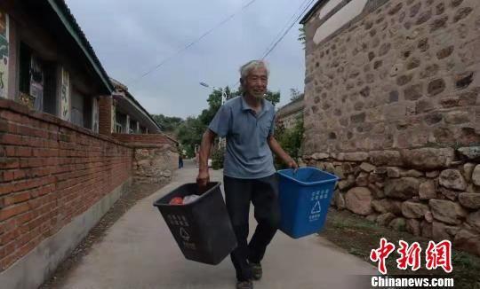 村民提着积攒一天的分类垃圾桶前往垃圾车倾倒 王天译 摄