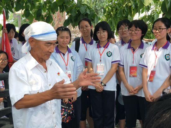 图为闫青海老党员在讲述西柏坡村的红色故事。