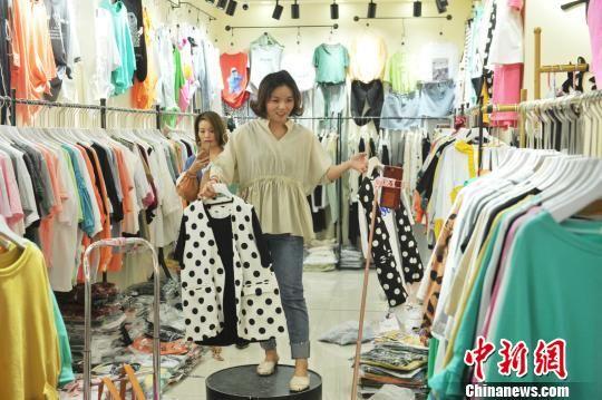 在明珠国际商贸城二期A区早市,来自北京的商户正在利用手机直播平台推销服装。 苑立伟 摄