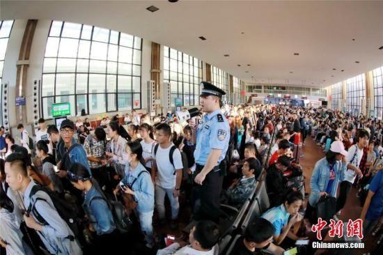 10月7日,河南郑州火车站、郑州东站迎来国庆假期返程客流高峰,车站内等待乘车的旅客熙熙攘攘。周延民 摄
