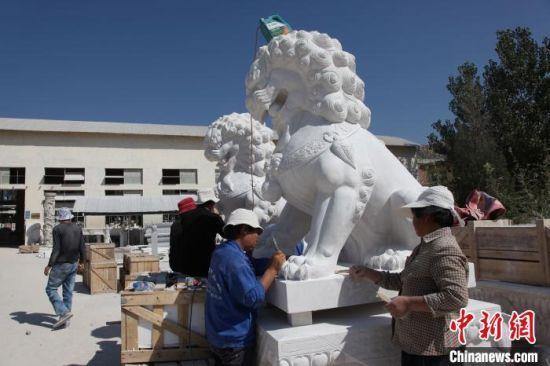石雕工人在对大型石狮作品举办润色加工。 刘玉峰 摄