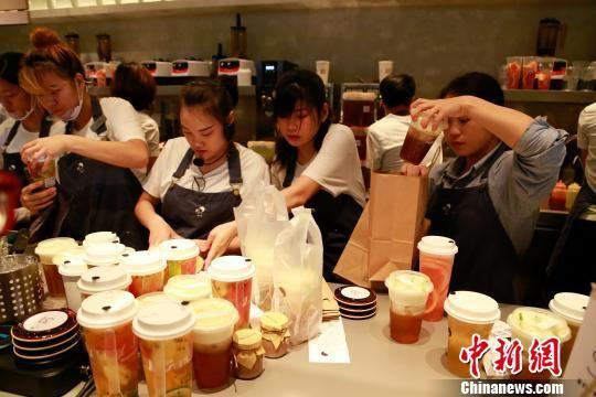 资料图:奶茶店员正在取餐处把饮料装袋。王远 摄