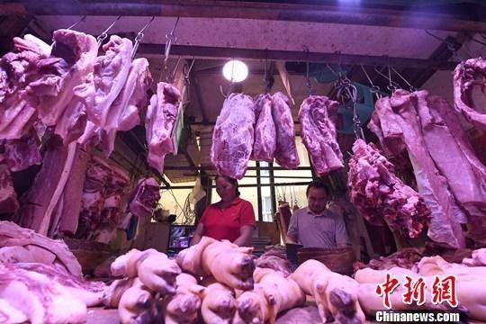 资料图:重庆主城区的一家农贸市场内,商贩正在摆放猪肉。中新社记者 陈超 摄