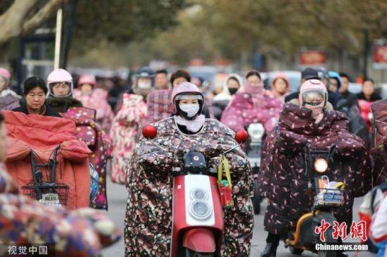 """资料图:天气降温,行人""""全副武装""""出行。图片来源:视觉中国"""