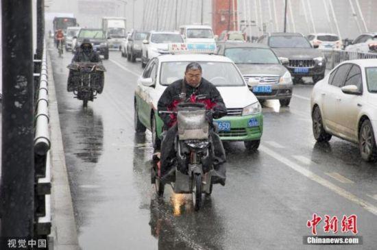 11月13日,吉林迎来入冬以来的首场降雪,市民冒雪出行。图片来源:视觉中国