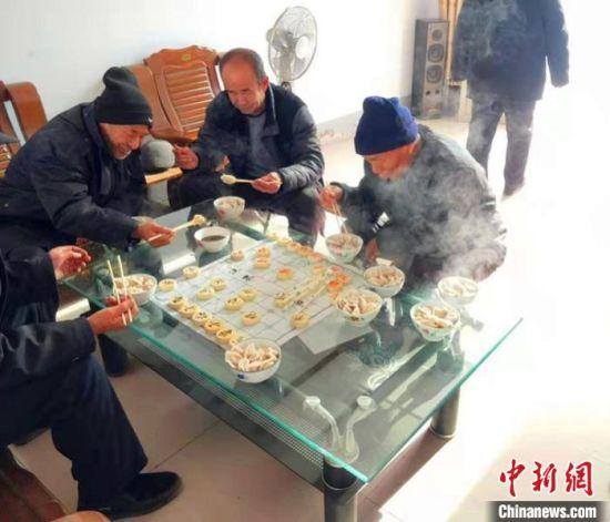 在平乡县柴口村的幸福小院里,老人在一边下棋一边吃饺子。 李铁锤 摄