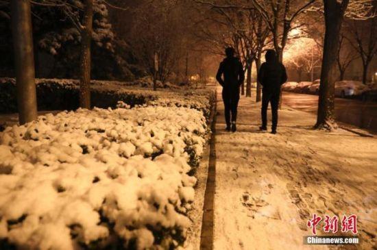1月5日晚,北京迎来2020年第一场雪。图为民众冒雪出行。中新社记者 赵隽 摄