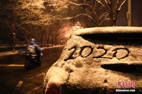 1月5日晚,北京迎来2020年第一场雪。图为民众冒雪出行。 中新社记者 赵隽 摄