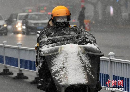 1月5日中午,河北石家庄迎来了2020年的第一场雪。图为市民雪中出行。中新社记者 翟羽佳 摄