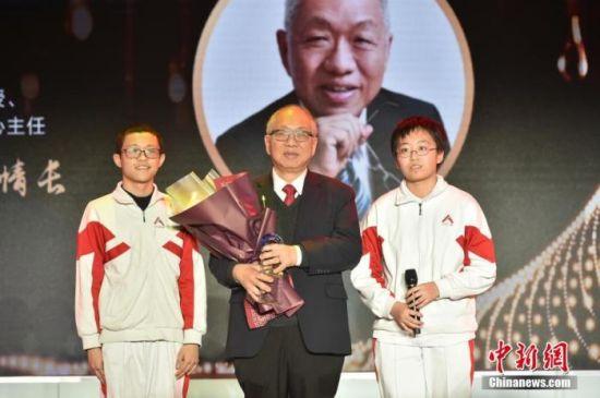 图为中国人民大学附属中学的两位同学为丘成桐献上奖杯,致敬杰出的华人数学家。中新社记者 翟璐 摄