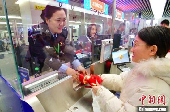 图为秦皇岛边检站执勤五队民警为入境旅客送新年吉祥物。 李金秋 摄