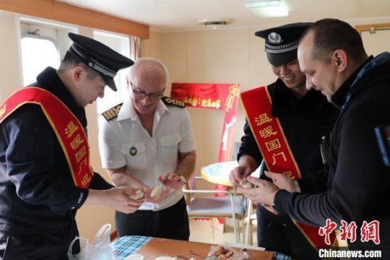 为秦皇岛边检站执勤一队民警与外籍船员一起包饺子迎新年。 李金秋 摄