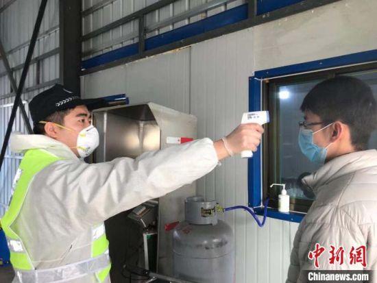 在阜平县生成桥搜检站,民警张文华对进入站点的人员举办体温检测。 阜平公安局供图 摄