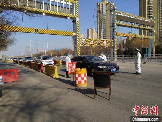 2月10日,河北复工第一天,从正定进入石家庄市区的车辆排起长队,工作人员依次检测车内人员体温。 翟羽佳 摄