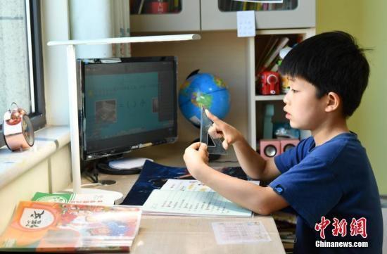 2月10日,河北石家庄,小学生们正在家中通过电脑、平板电脑等收看直播上课。中新社记者 翟羽佳 摄