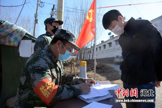 曲阳东赵厂村退役武士在路口对行人检查登记。 郭英�j 摄