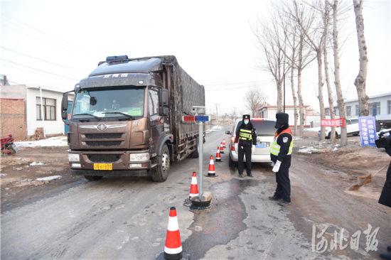 疫情防控检查站工作人员对过往车辆进行登记、检查。