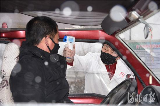 疫情防控检查站工作人员对过往车辆和人员展开登记和体温检测。