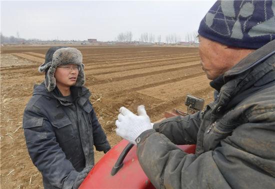 3月1日,陶向琳(左)在田間與社員交流。