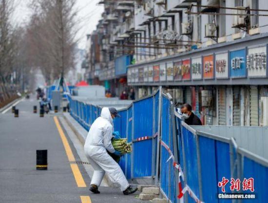 3月6日,武汉汉阳鹦鹉大道,志愿者正在给居民送生活物资 。中新社记者 张畅 摄