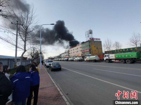 图为火灾发生后,几名化工厂员工站在路旁。 王天译 摄