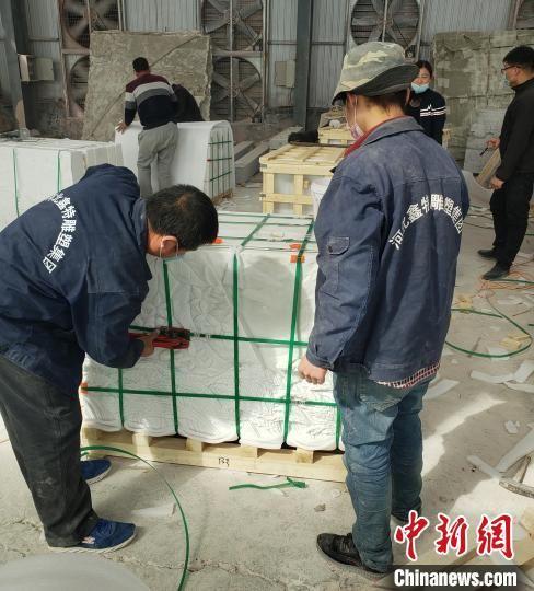 工人们在对验收后的《埃塞赞歌》浮雕墙分包装箱。 薄丽丽 摄